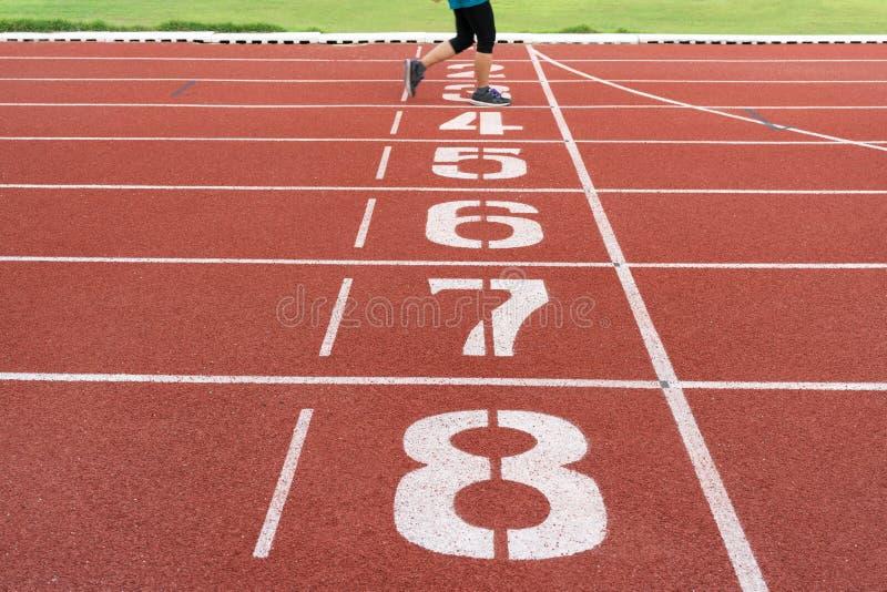 Номера на красном идущем следе с ногами бегуна Пункт начала и финиша трассы в стадионе стоковая фотография rf