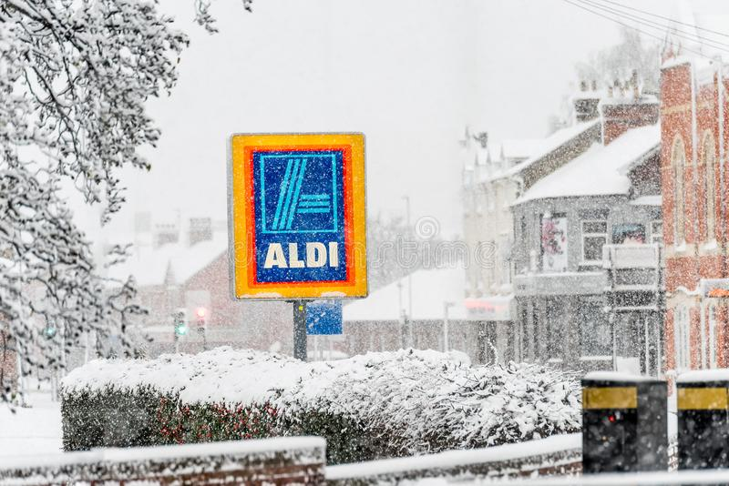 Нортгемптон Великобритания 10-ое декабря 2017: Знак логотипа Aldi под тяжелым снегом зимы в центре Northampton Town стоковое изображение