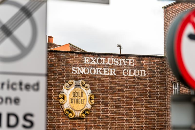 Нортгемптон Великобритания 5-ое января 2018: Исключительная стойка знака логотипа улицы золота клуба снукера в центре Northampton стоковое фото rf