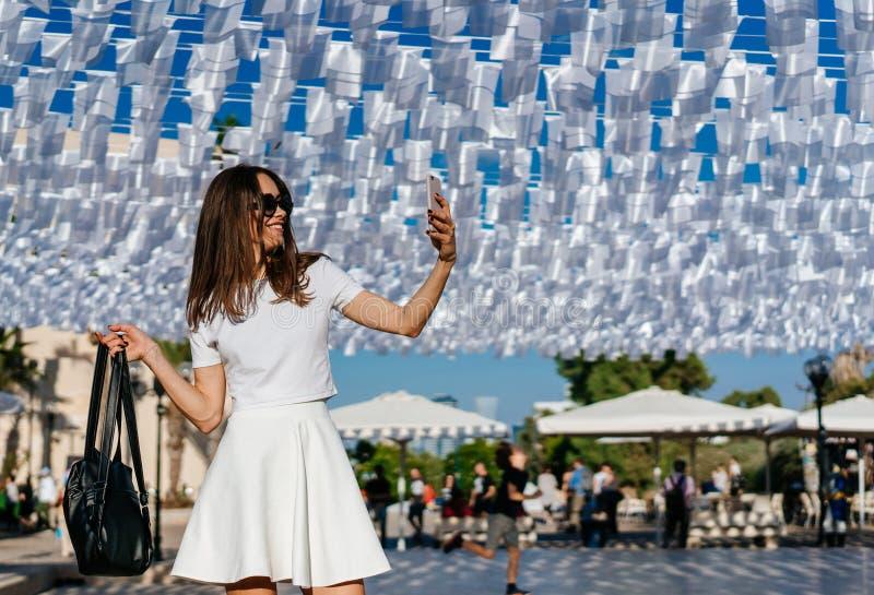 Носка брюнет красивой женщины молодая в белом платье стоковая фотография