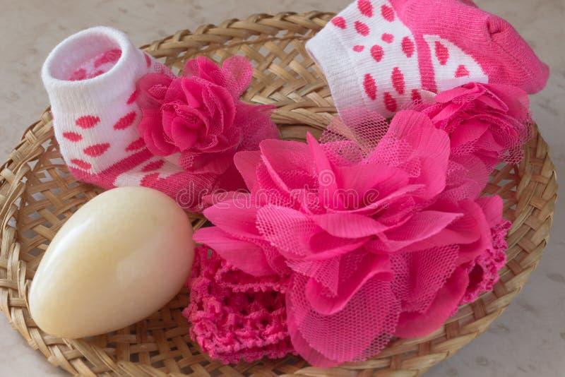 Носки младенца, розовый цветок, желтое яичко в плетеной плите на таблице стоковые фотографии rf