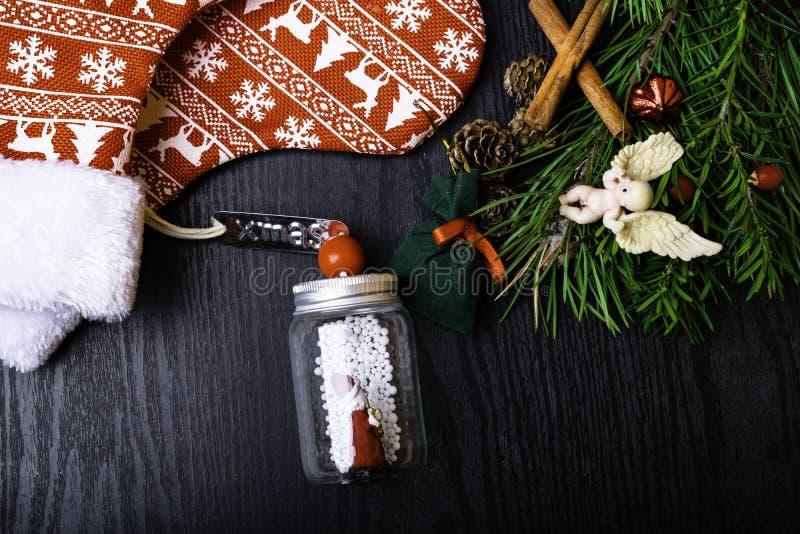 Носки рождества с присутствующим подарком, Санта Клаусом, циннамоном Чулок и игрушки украшения рождества вися над деревянной пред стоковая фотография rf