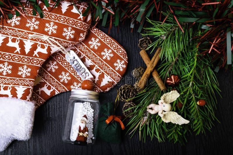 Носки рождества с присутствующим подарком, Санта Клаусом, циннамоном Чулок и игрушки украшения рождества вися над деревянной пред стоковое фото