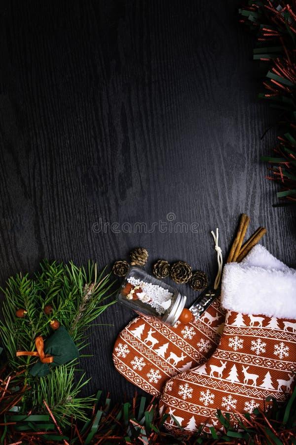 Носки рождества с присутствующим подарком, Санта Клаусом, циннамоном Чулок и игрушки украшения рождества вися над деревянной пред стоковые изображения