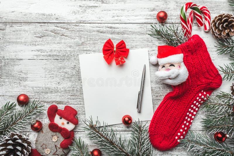 Носок рождества с настоящими моментами Чулок и игрушки украшения рождества вися над серой деревенской деревянной предпосылкой стоковые фото