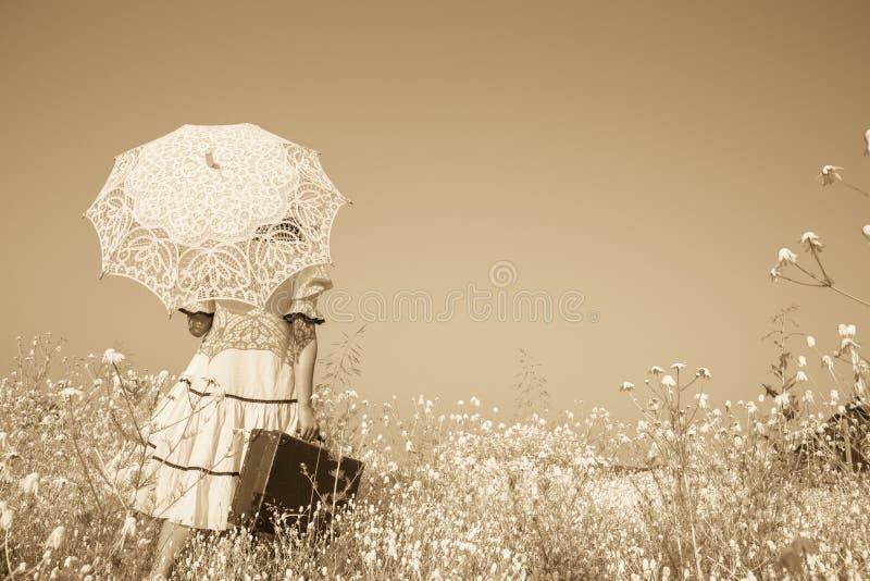 Ностальгическое старое фото в цвете sepia Девушка с ее walki зонтика стоковые фото