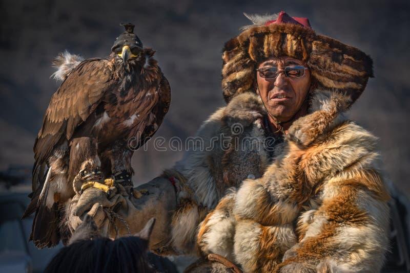 Носящий очки опытный монгольский кочевник в меховой шыбе Fox, одном из участников фестиваля беркута Человек в стеклах с Gol стоковая фотография rf
