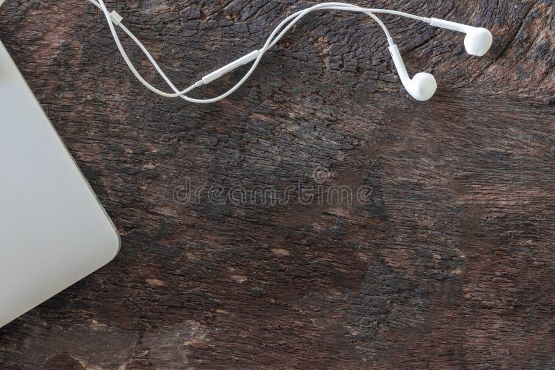 Ноутбук и наушник взгляда сверху на старой деревянной предпосылке с космосом экземпляра стоковая фотография