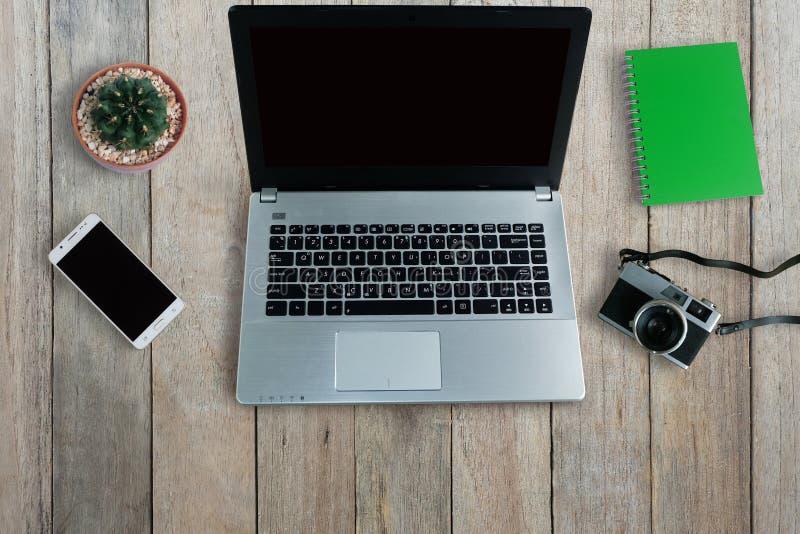 Ноутбук и умная камера телефона и старых фильма использовали устройства электроники на деревянном поле стоковые изображения