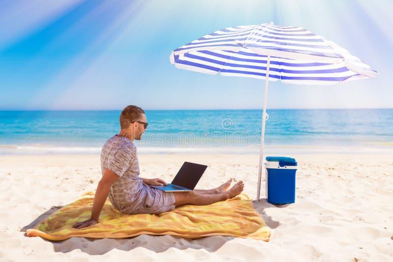 Ноутбук молодого красивого человека lusing на стенде пляжа с голубым солнечным зонтиком наверху, окруженный морем бирюзы и стоковое фото rf