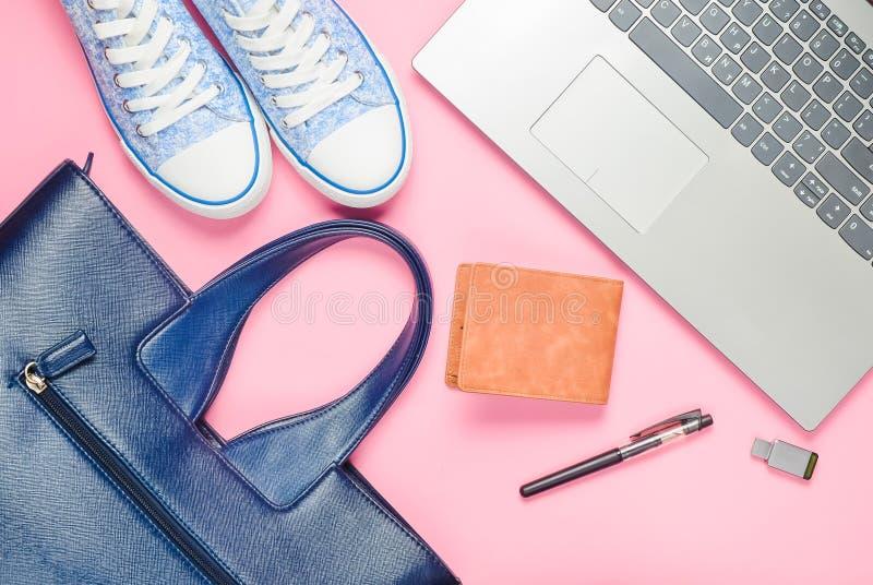 Ноутбук, привод usb внезапный и модные женские аксессуары на розовой предпосылке: сумка, бумажник, тапки, сумка Взгляд сверху Пло стоковые изображения