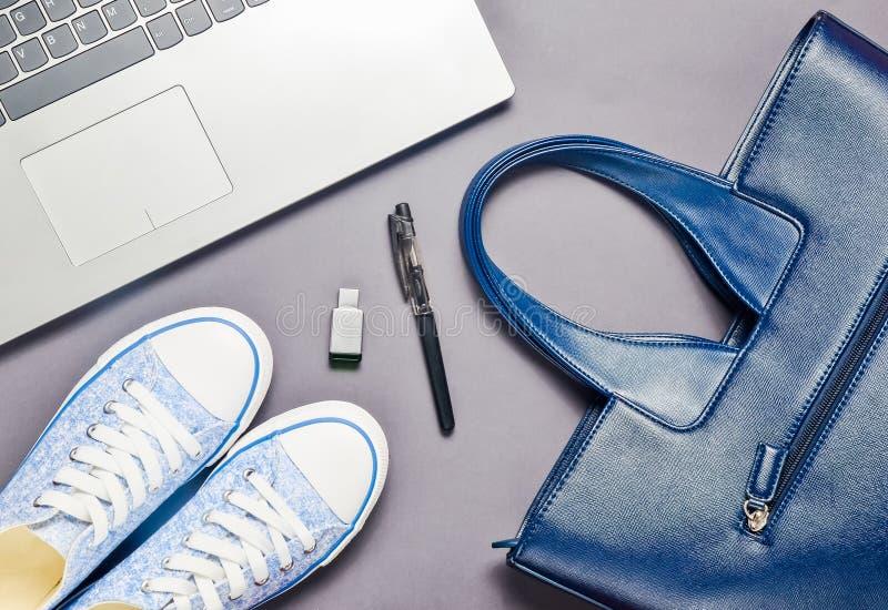 Ноутбук, привод usb внезапный и модные женские аксессуары на серой предпосылке: сумка, бумажник, тапки, сумка Взгляд сверху Плоск стоковая фотография