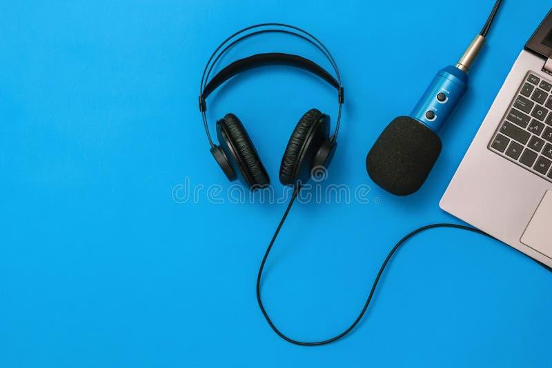 Ноутбук с соединенным микрофоном и наушниками на голубой предпосылке Концепция организации рабочего места r стоковое изображение