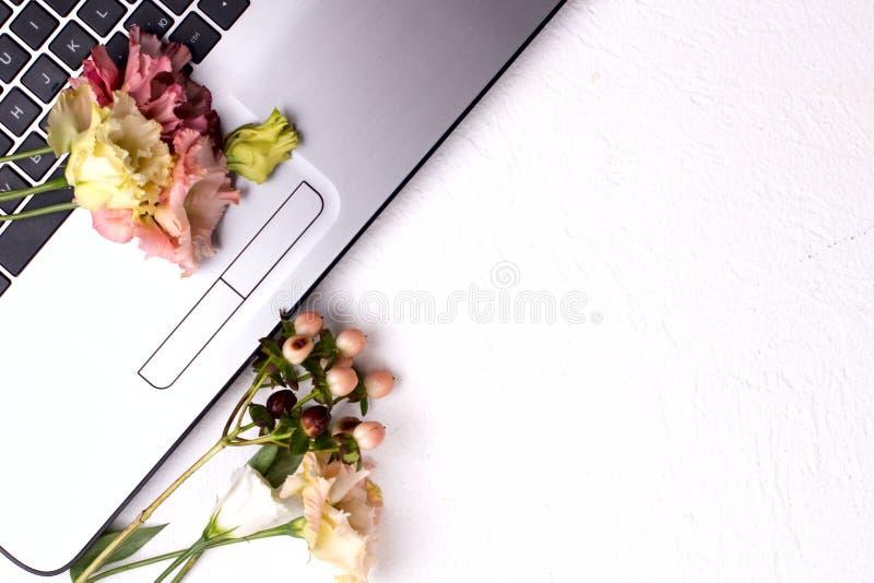 Ноутбук с цветами и косметикой на белом столе Рабочая область Freelancer стоковые изображения