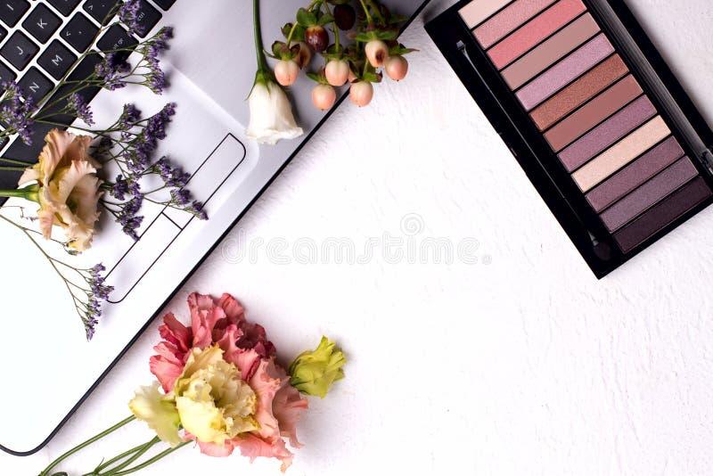 Ноутбук с цветами и косметикой на белом столе Рабочая область Freelancer стоковое изображение rf