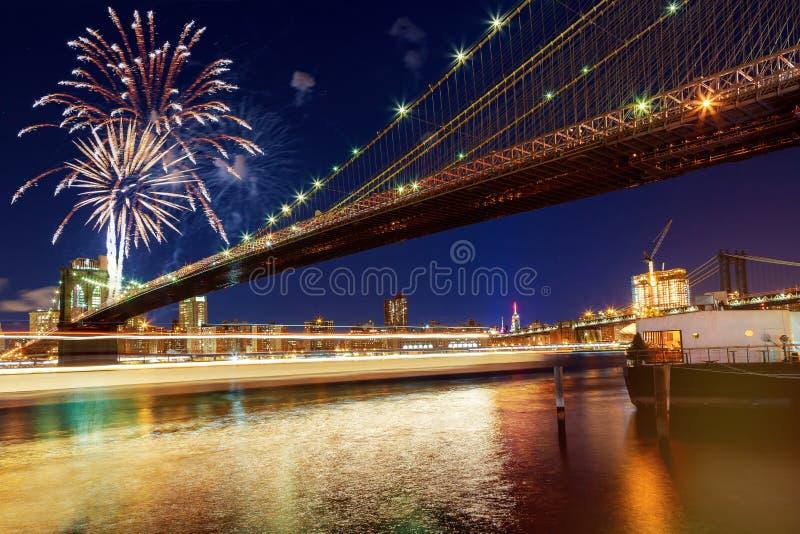 Ноча Гудзон изумительного горизонта Бруклинского моста и Манхаттана Нью-Йорка фейерверков торжества стоковое фото rf