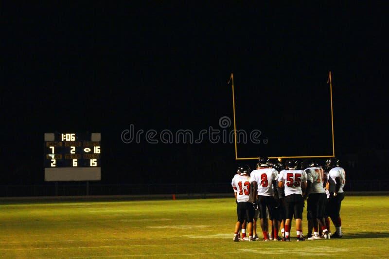 ноча huddle футбольной игры стоковые фотографии rf