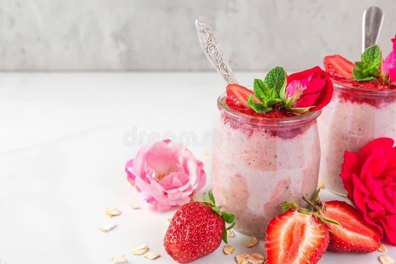 Ночные овсы или каша овсяной каши со свежими клубниками и мятой в стеклах с розовыми цветками и ложками стоковая фотография