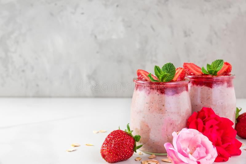 Ночные овсы или каша овсяной каши со свежими клубниками и мятой в стеклах с розовыми цветками на белой мраморной таблице стоковая фотография rf
