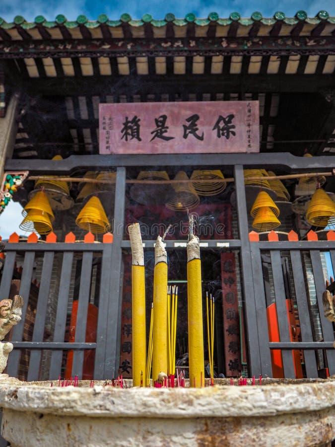 Ноябрь 2018 - Макао, Китай: Желтое горение ладана перед небольшим одним виском Na Tcha одноместного номера за руинами St стоковое фото