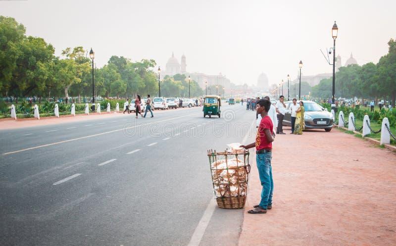 Нью-Дели, Индия - 1-ое июня 2019: Маленький ребенок продавая закуски около Rashtrapati Bhawan на улицах стоковые фото