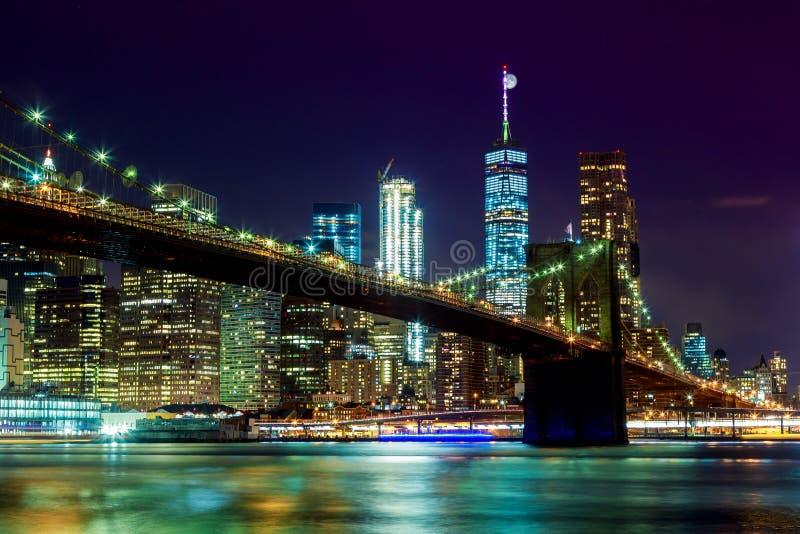 Нью-Йорк & x27; горизонт Бруклинского моста и Манхаттана s осветил накладные расходы полнолуния стоковое изображение rf