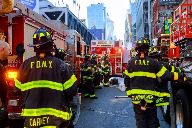 НЬЮ-ЙОРК - 15-ое июня 2018: Отделения пожарной охраны нагнетают топливо от автомобиля после аварии стоковые фото