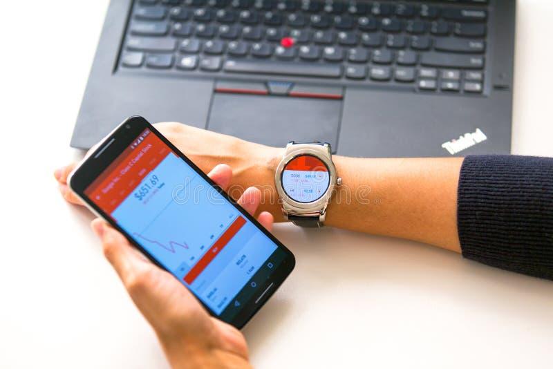 Нью-Йорк, США - 20-ое августа 2015: Бизнес-леди смотрящ котировки акций на ее smartwatch стоковая фотография