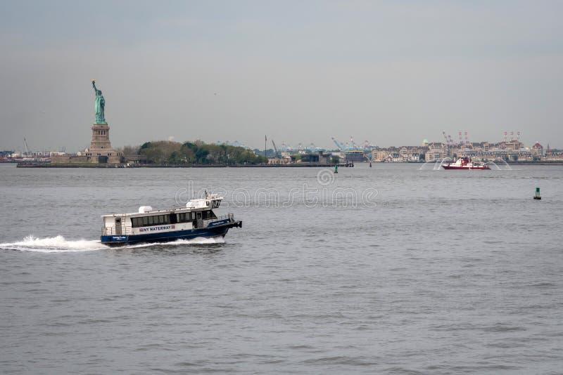 Нью-Йорк, США - 7-ое июня 2019: Паром причаливая статуе свободы, острову свободы - изображению стоковое изображение