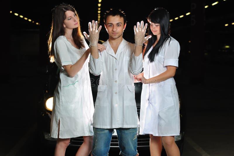 Нюни помогают хирургу одетьть перчатки стоковые фотографии rf