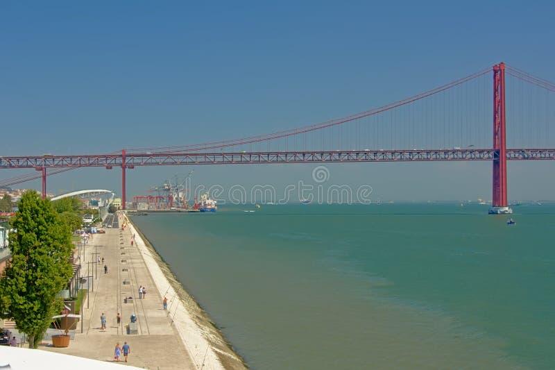 Обваловка реки Тахо и мост 25-ое апреля в порте Лиссабона, стоковое изображение