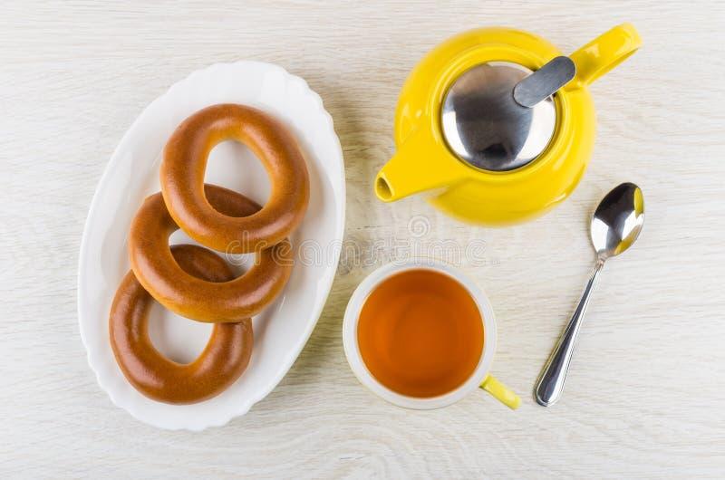Обваляйте кольца в сухарях в блюде, чайнике, чае и ложке на таблице стоковые изображения rf