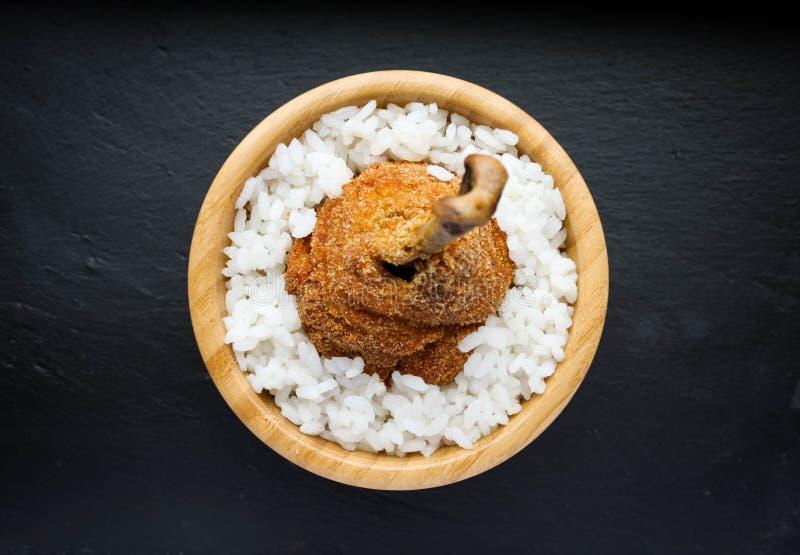 Обвалянная в сухарях нога жареной курицы с белым рисом стоковое фото