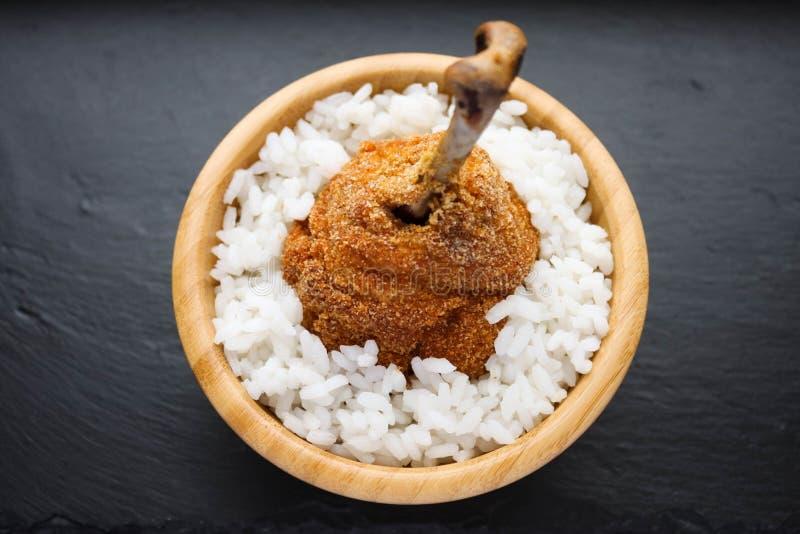 Обвалянная в сухарях нога жареной курицы с белым рисом стоковые фото