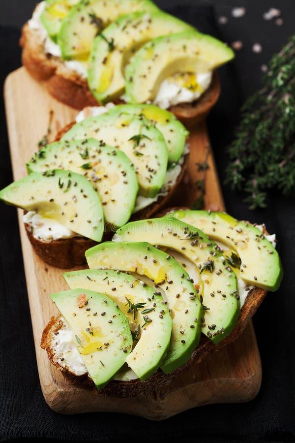 Обваляйте куски в сухарях с сметанообразными сыром и авокадоом на деревянной разделочной доске для здоровой закуски стоковое фото