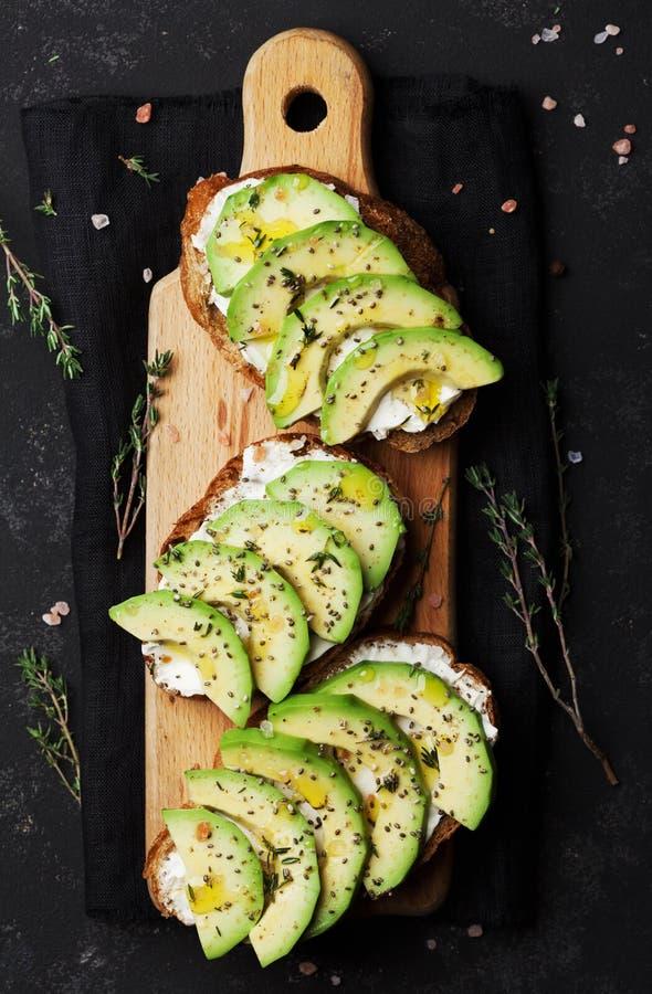 Обваляйте куски в сухарях с сметанообразными сыром и авокадоом на деревянной разделочной доске сверху для здоровой закуски стоковые изображения rf