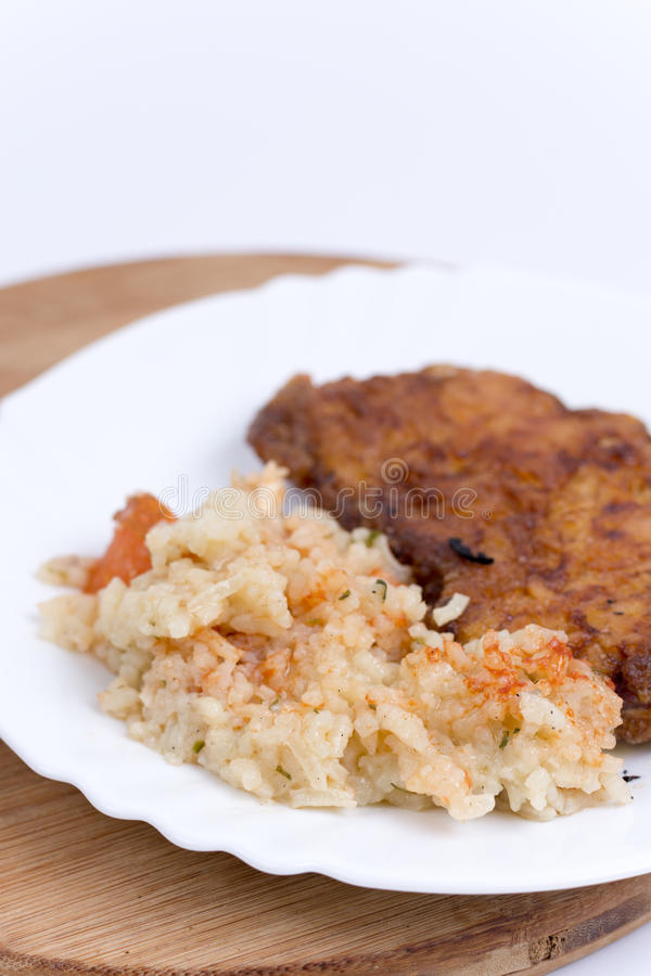 Обвалянное в сухарях мясо с сваренным рисом с овощами стоковое фото