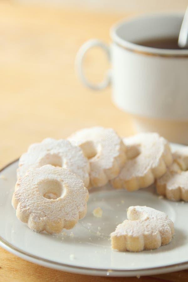 Обгрызенные печенья Canestrelli итальянки около чашки черного чая стоковая фотография