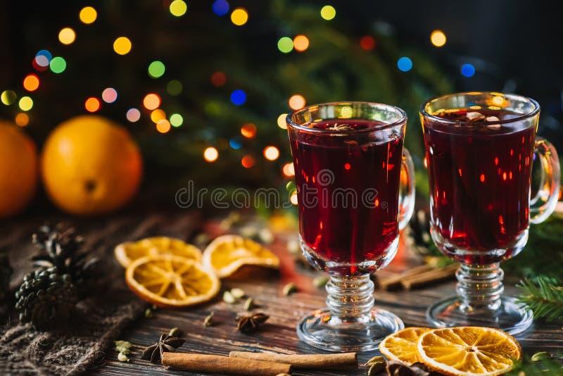 Обдумыванное вино в стеклянных стеклах с апельсином, циннамоном, кардамоном, звездами анисовки на таблице украшенной с рождествен стоковые фотографии rf