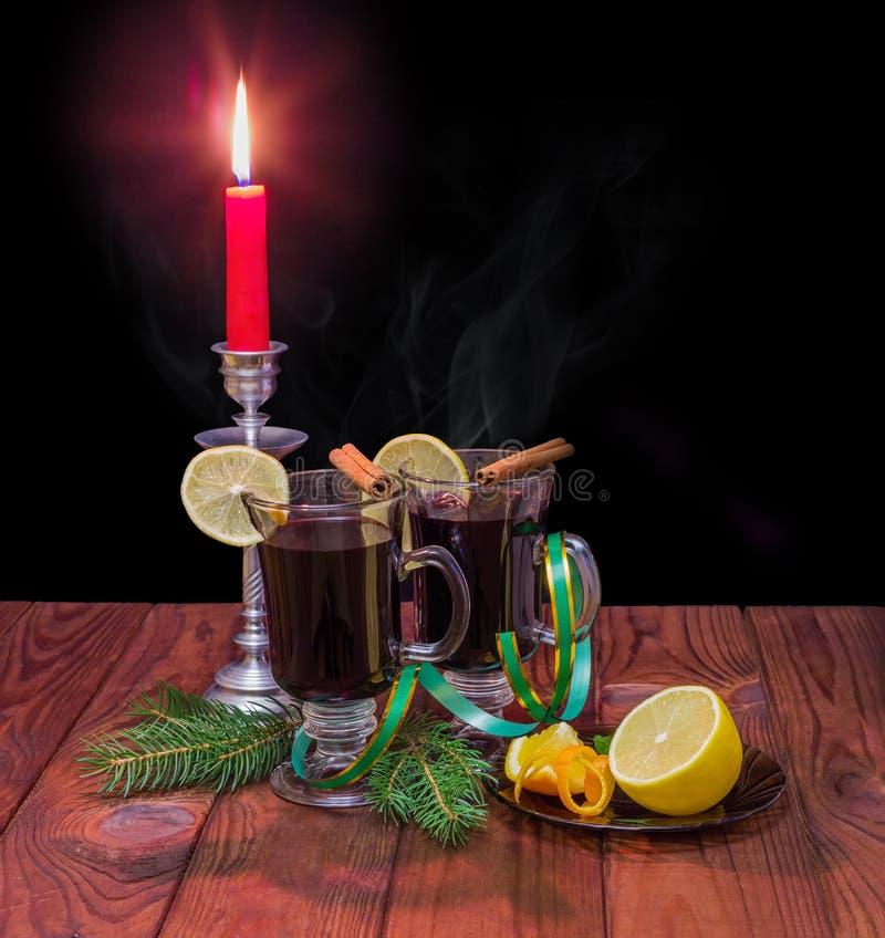 Обдумыванное вино с обдумывать специи, елевые ветви, горя свечу стоковая фотография