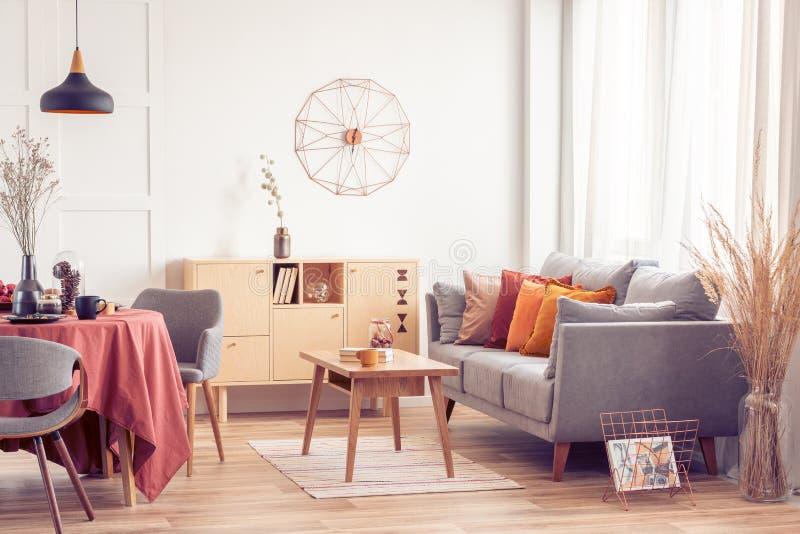 Обедать и жилая площадь открытого пространства с серыми скандинавскими софой и таблицей со стульями стоковая фотография rf