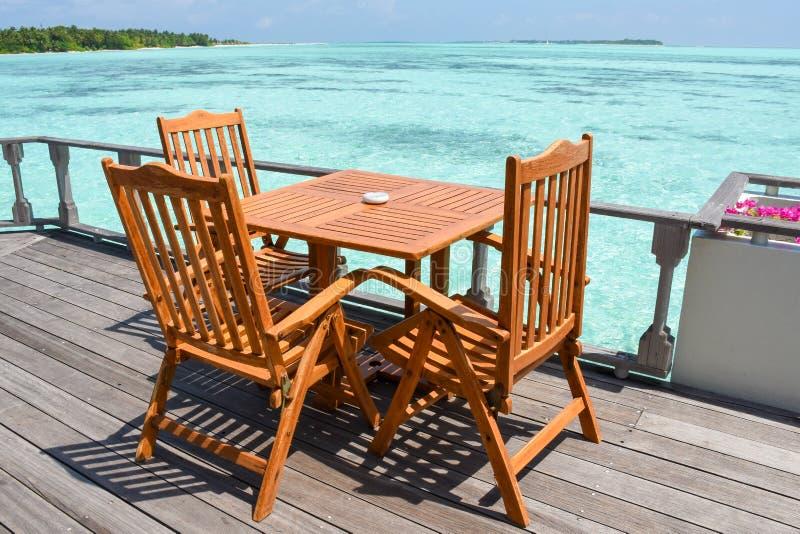 Обедать установка с деревянными столами и стульями на ресторане около океана на курорте стоковое изображение rf
