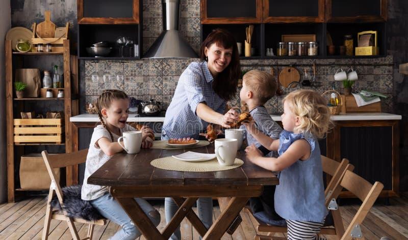 Обедающий семьи: Мама распределяет сладкие торты чая для десерта до 3 дет стоковая фотография rf