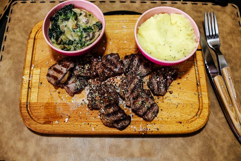 Обедающий тонко отрезанного мяса ‹â€ ‹â€ с картофельными пюре и соусом служил на деревянном подносе стоковое фото