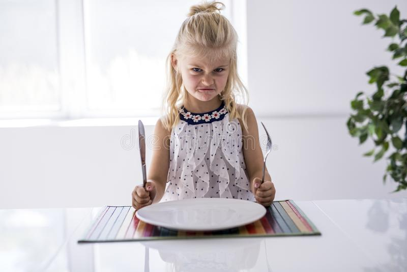 Обедающий яростной маленькой девочки ждать Удержание вилки в руке стоковое изображение rf