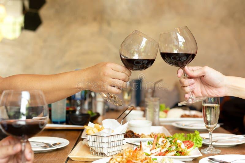 Обед торжества друзей с руками провозглашая тост стеклянное красное вино с едой стоковое изображение