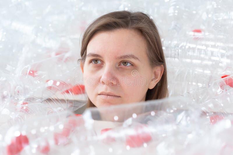 Обезвоженная больная женщина лежит в куче пластиковых бутылок Проблема загрязнения окружающей среды Отброс природы стопа стоковые фото