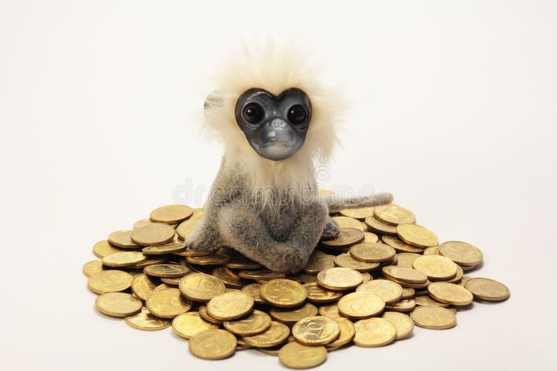 Обезьяна сидит на куче золотых монеток стоковое фото