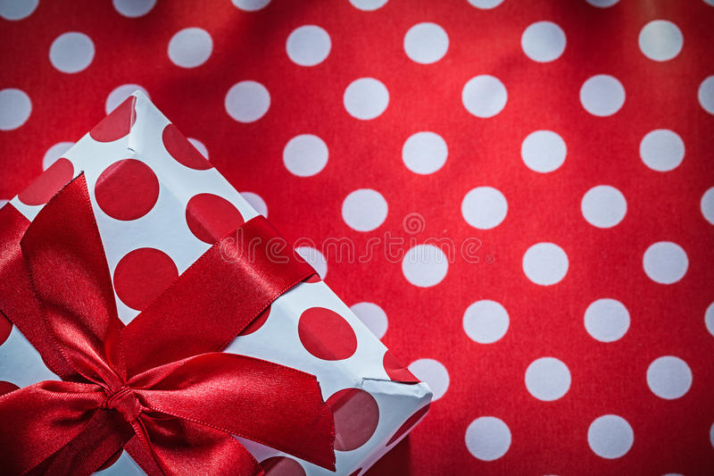 Обернутая присутствующая коробка с смычком на holida ткани таблицы полька-точки красном стоковое фото rf