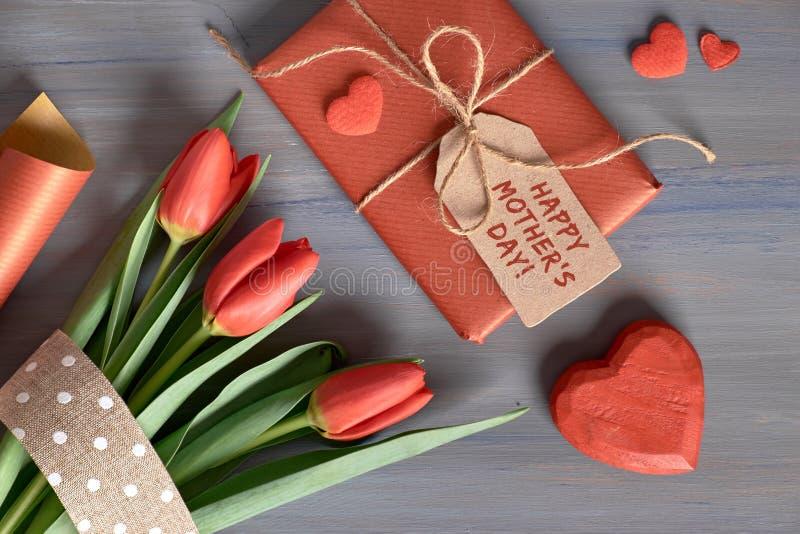 Обернутые тюльпаны подарка красные, упаковочная бумага и декоративные сердца дальше стоковые изображения rf